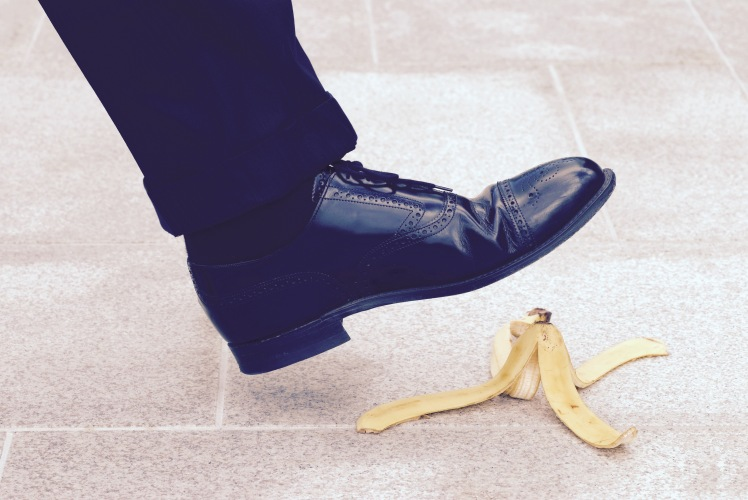 Businessman stepping on banana skin